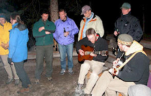 Information exchange continues around the campfire at Blue Lake. Left to right, standing: Jackie Morris, Karen Bray, Chris Steeger, Patrick Daigle, Larry Halverson, Murray Peterson. Musicians: Ian Adams and Rob Walker. Doug Adama photo.