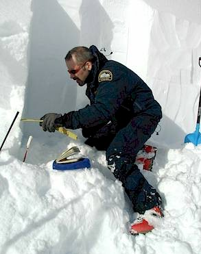 John Kelly examines snowpack structure in a snow pit. Bruce McMahon / Parks Canada photo